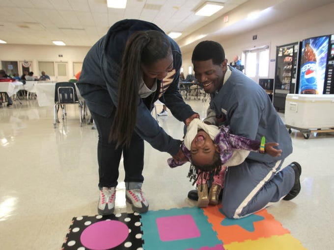 Inmate Bernard Smith has playtime with daughter Shaquita Smith, left, and granddaughter Khloe Cash, 1, Friday at the Charlotte Correctional Institution in Punta Gorda.