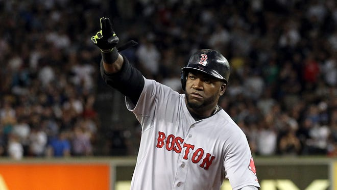 Boston Red Sox designated hitter David Ortiz (34) celebrates while rounding the bases after hitting a three-run home run against the New York Yankees during the third inning at Yankee Stadium.