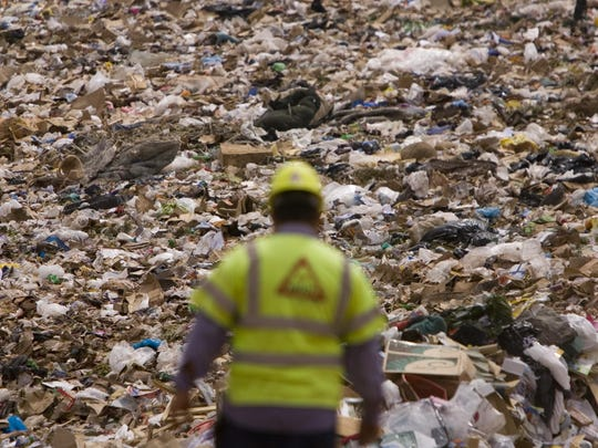 Waste piles up above a Washington County Solid Waste District employee in this Spectrum Media file photo. Local communities are planning to implement a new curbside recycling program by early 2016.