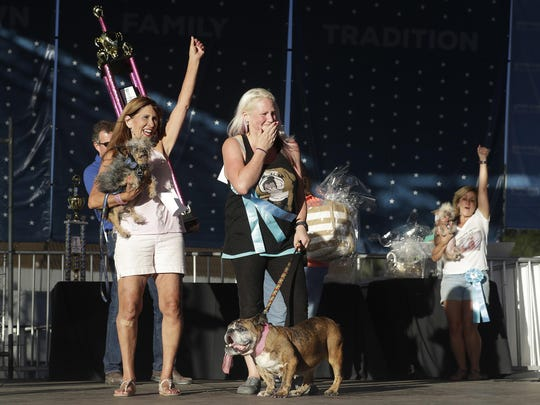 Megan Brainard, center, reacts after her dog Zsa Zsa, an English Bulldog, bottom, is announced the winner of the World's Ugliest Dog Contest.