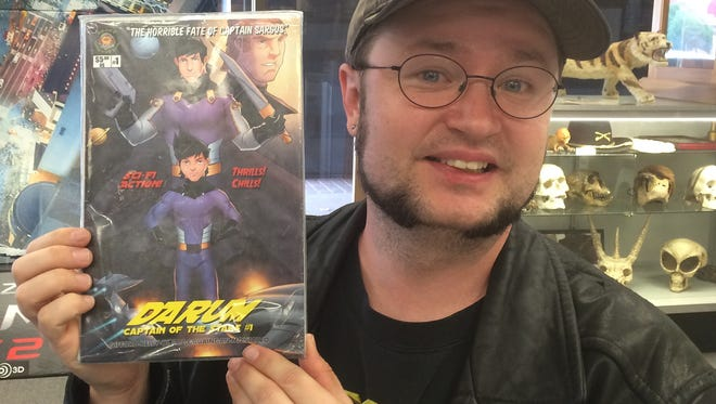 "Author Jared Gifford holds up the first issue of his comic book, ""Darum: Captain of the Stars."""