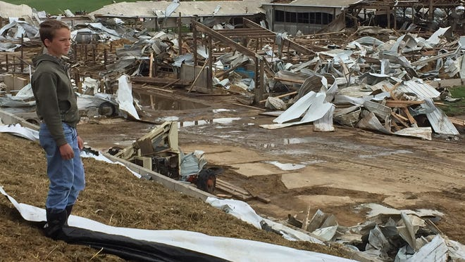 Daniel Zimmerman, of Snover looks over the debris of the destroyed barns at the de Vor dairy farm on June 23, 2015, in Lamotte Township. A statewide tornado drill will be Wednesday.