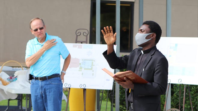 Father Theodore Agba, right, offers a blessing for the St. Teresa of Avila building project earlier this week as parishioner and project leader Jerry Baine listens. The church is constructing a 37,000-square-foot addition to its Life Center to give a dedicated home for its youth ministries.