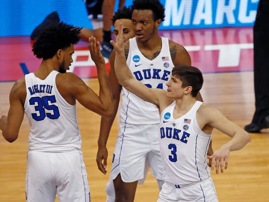 Duke's Grayson Allen, right,  celebrates making a three-point shot with Marvin Bagley III, left, and Wendell Carter Jr, center, during the first half of an NCAA men's college basketball tournament second-round game against Rhode Island, in Pittsburgh, Saturday, March 17, 2018. (AP Photo/Gene J. Puskar)