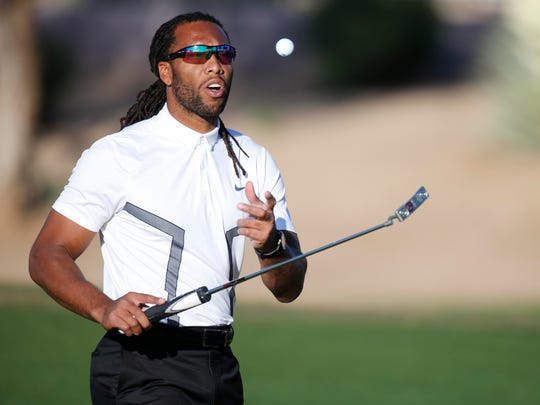 Larry Fitzgerald grabs his golf ball after putting during the LPGA JTBC Founders Cup Pro-Am at the Wildfire Golf Club in Phoenix Ariz., Wednesday, March 16, 2016.