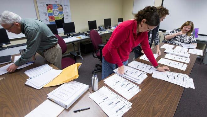 Workers sort absentee ballots as part of the Wisconsin recount  Thursday at the Iowa County Courthouse in Dodgeville. Thursday was the first day of recounting ballots from the presidential election. Green Party presidential candidate Jill Stein raised to pay the $3.5 million for the massive recount.