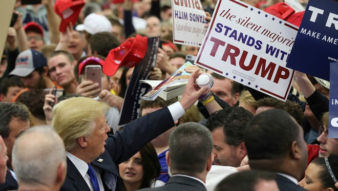 Trump supporters crowd a rope line at the end of the rally to have Donald Trump autograph signs, books, balls and dollar bills.