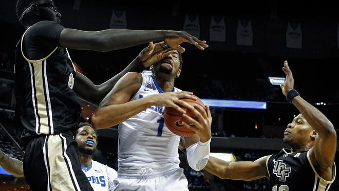 University of Memphis forward Dedric Lawson (middle) takes a shot to the face while driving to the basket against University of Central Florida defenders Taco Fall (left) and Matt Williams (right) of Feb. 17, 2016.