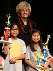 Winners of the Deming Public Schools District-Wide Spelling Bee were, from left, Zachary Cruz, second place; and Franchesca Coloma, first place. Suzanne Lundy was the district's pronouncer.