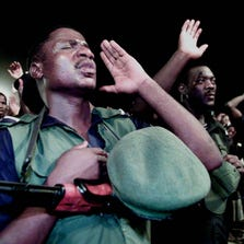 A policeman prays with Reinhard Bonnke for the healing of his physical ailment during a 2001 crusade in Nigeria.