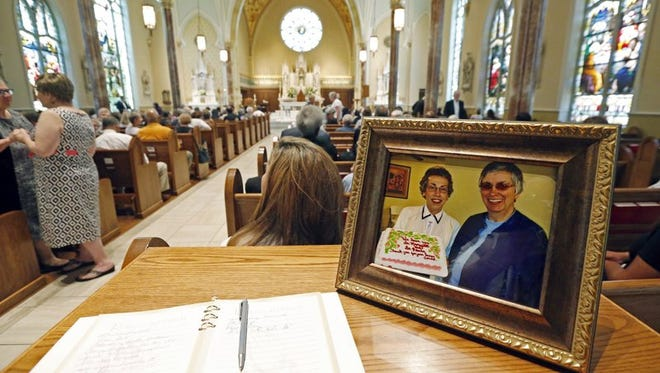 In this Aug. 29, 2016, file photo, a photograph showing Sisters Margaret Held, left, of the School Sisters of St. Francis, and Paula Merrill, of the Sisters of Charity of Nazareth, sits at the entrance of a cathedral in Jackson, Miss., where a memorial was held for the two 68-year-old nuns.
