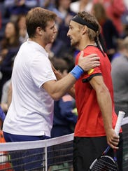 Ryan Harrison, of the United States, left, is congratulated by Ruben Bemelmans, of Belgium, after Harrison won their Davis Cup quarterfinal singles tennis match Sunday, April 8, 2018, in Nashville, Tenn. The United States clinched the series Saturday to move on to the semifinals. (AP Photo/Mark Humphrey)