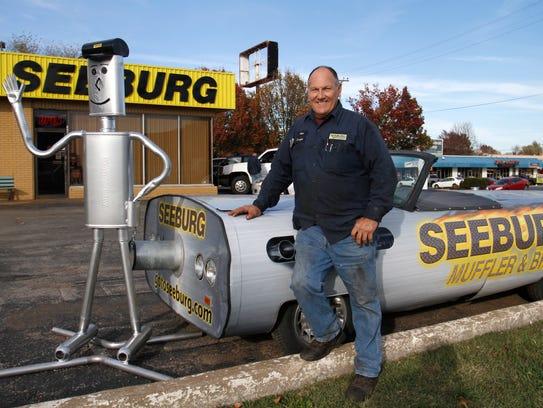 Gene Sneed with his muffler car and muffler man creations
