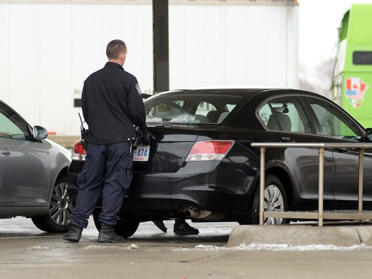 Customs and Border Protection officer searches a car