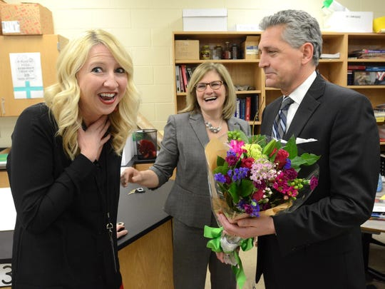 Novi Middle School science teacher Sarah David is surprised Monday by school Principal Stephanie Shriner and Novi Educational Foundation chairman Tom Smith as she's named district Teacher of the Year. David won a two-year lease on a car from the Suburban Collection, too.