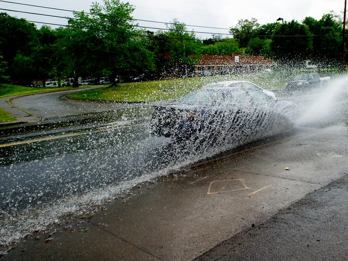 A vehicle drives through a large puddle of water on