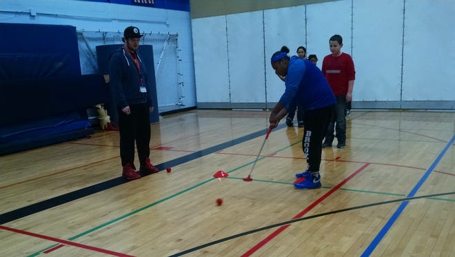 Staff member R.J. Avery, left, looks on as students putt at the First Tee of Corning's DRIVE program at the Boys & Girls Club of Western Broome, in Endicott.