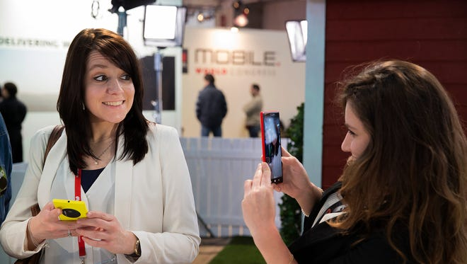 A woman takes a picture with a Nokia Lumia 1520 phone as her friend smiles at the Mobile World Congress in Barcelona, Spain. The latest wave of smartphones will include cameras that closely match higher-end rivals.