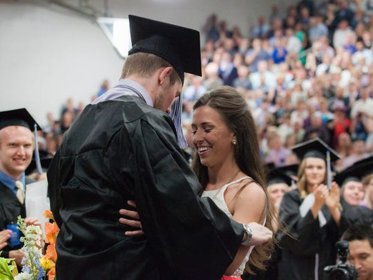 Chris Norton graduates with the class of 2015 and walks across the stage to receive his diploma with the assistance of his girlfriend and a standing ovation from the crowd.