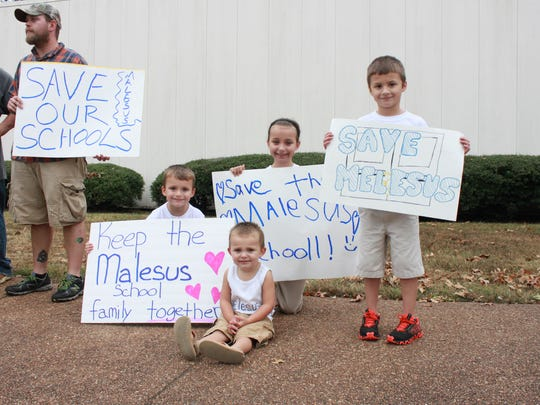 Blayne Mayo, Brilee Mayo, Gavin Wimberley and Parker Mayo hold signs supporting Malesus Elementary School outside the school system's central office Monday.