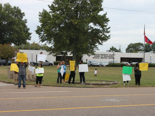 Community members line North Parkway in front of the school system's central office to protest Vision 2020 on Monday.