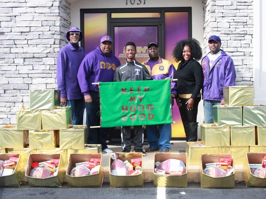 Alvino Douglass, Don Lloyd, Corey Currie, Jerry Butler, Juanita Jones and Clayton Phillips stand with boxes of Thanksgiving food to be given to families from the Omega Psi Phi Fraternity.