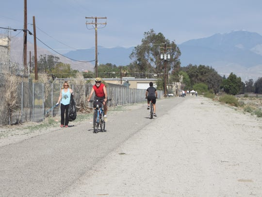 Bicyclists move past a volunteer during a Sunday cleanup