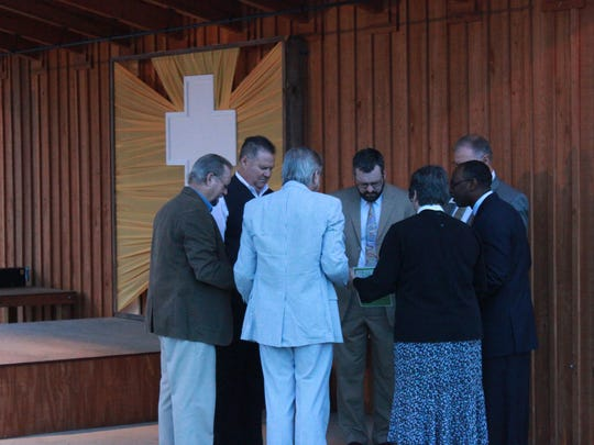 Leaders from three churches pray together before a joint Easter Sunday Sunrise Service at the downtown AMP.