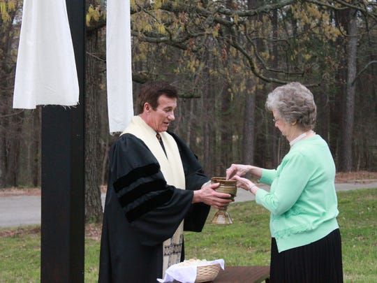 The Rev. Barry Scott offers the communion cup to Katharyne Alexander Sunday outside Aldersgate United Methodist Church.