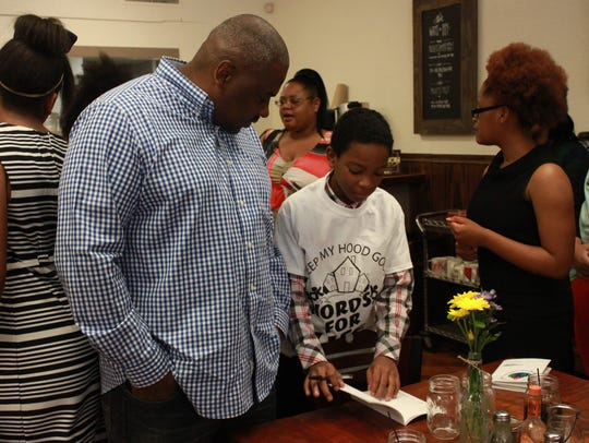 Kaden Rogers, 13, signs a copy of 'Words for Life'