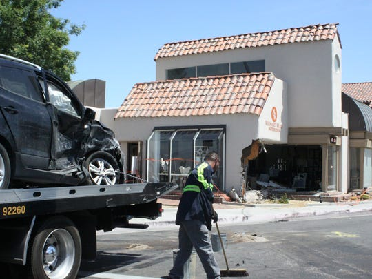 A Hyundai is prepared for removal while a tow truck driver sweeps debris from the scene of a collision that sent one car into a Palm Desert business Sunday afternoon.