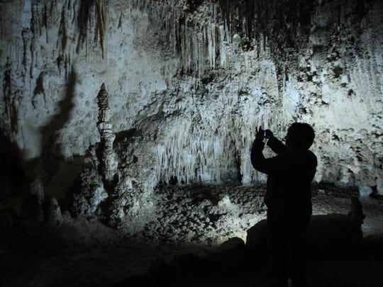 A visitor takes a photo of a cave formation at King's