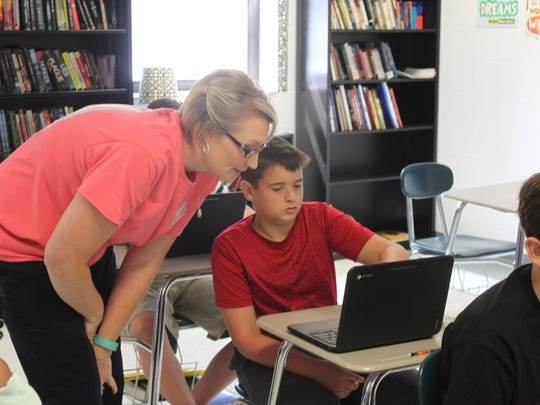 Lorrie Vinson helps Kyle Brown with material on his new Chromebook at Huntingdon Middle School.