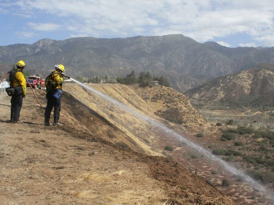 Cal Fire firefighters put out hot spots in the Banning Bench, which was scorched by the Bogart Fire. At least 1,300 acres were burned by the fire, which officials say was human caused.