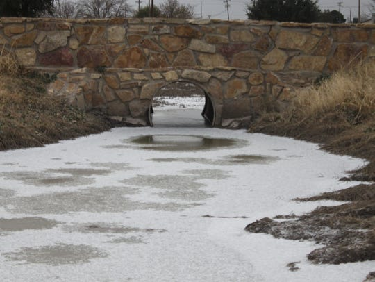A small creek is frozen and coated with a thin layer