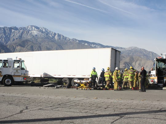 Firefighters try to free a woman trapped in an SUV that became lodged under a big rig trailer. The crash blocked Indian Canyon Drive at Interstate 10 Sunday in Palm Springs.