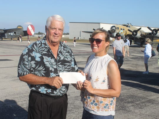 Glenn Stevens, left, a LaPlaya club member, presents a check of an estimated $4,600 to Jamie Mitchell with The Collings Foundation at the Naples Municipal Airport. Stevens and other members with the local golf club donated the money in honor of Bill Heck, WWII veteran.