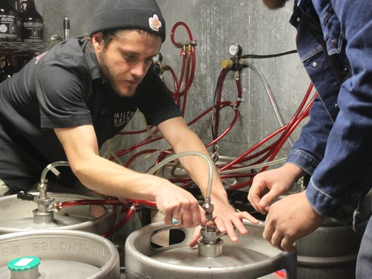Jameson Lucas taps a keg in the keg room Friday at Milton's Brewing.