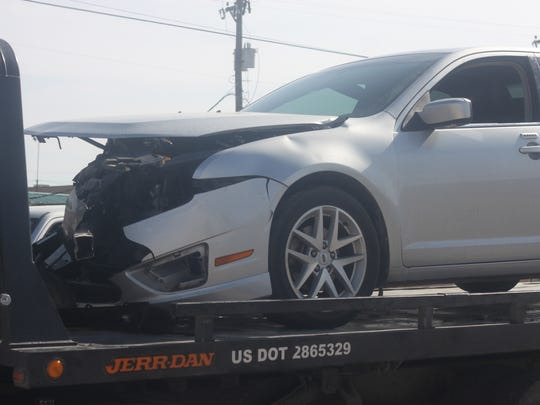 A Ford Fusion sits atop a flatbed tow truck after a