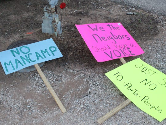 Residents carried signs protesting a new man camp Monday