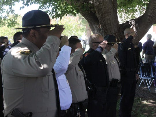 Officers salute the flag during a color guard presentation at a law enforcement memorial Tuesday at the Pecos River Village Conference Center.