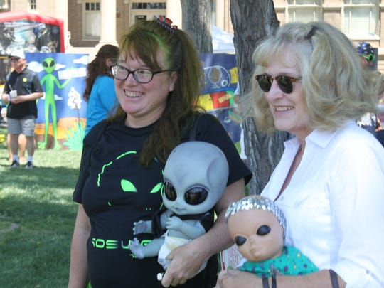 Patrons visit with outdoor vendors sporting Alien-theme merchandise during the Roswell UFO Festival, Friday in downtown Roswell.