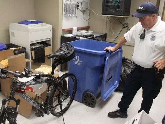 Cpl. Alan Franzoy of the Carlsbad Police Department inspects a bike in a storage area Thursday at the station. This bike is not one of about 20 the department is looking to return to owners.