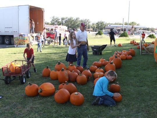 Volunteers receive a shipment of pumpkins Thursday