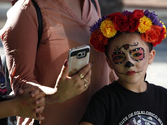 Seven-year-old Sofie Aguilar, attends the Dia de los Muertos Festival in Mesa dressed as a catrina.