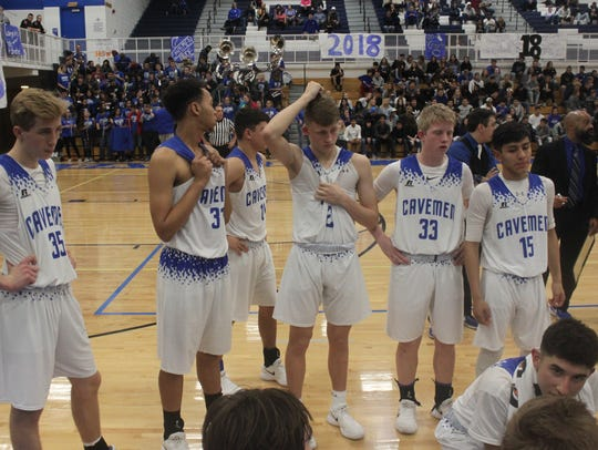 The Carlsbad Cavemen confer with the coaching staff