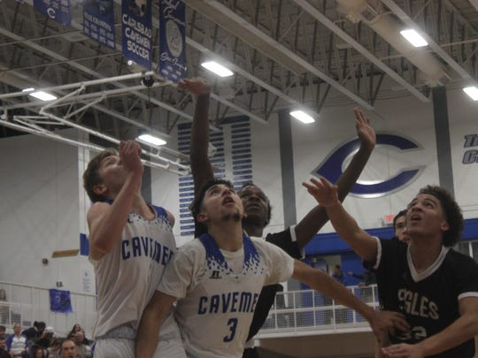 The Cavemen fight for a rebound in a game against Hobbs,