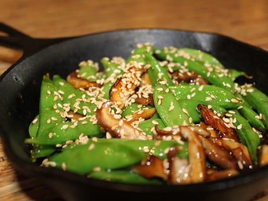 An order of glazed sesame peas with shitake mushrooms.