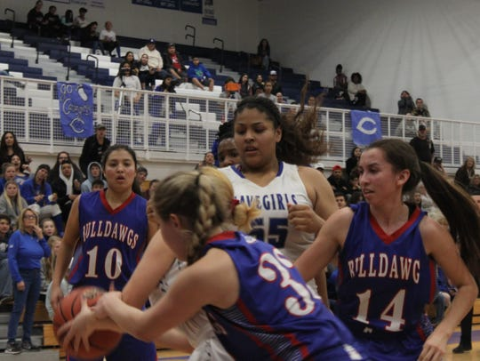 Carlsbad center Kaliyah Montoya contends with several