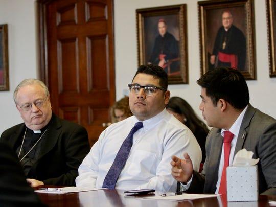 Edgar Trinidad (r) shares his story with Bishop Dennis Sullivan as Luis Botello (center) listens.